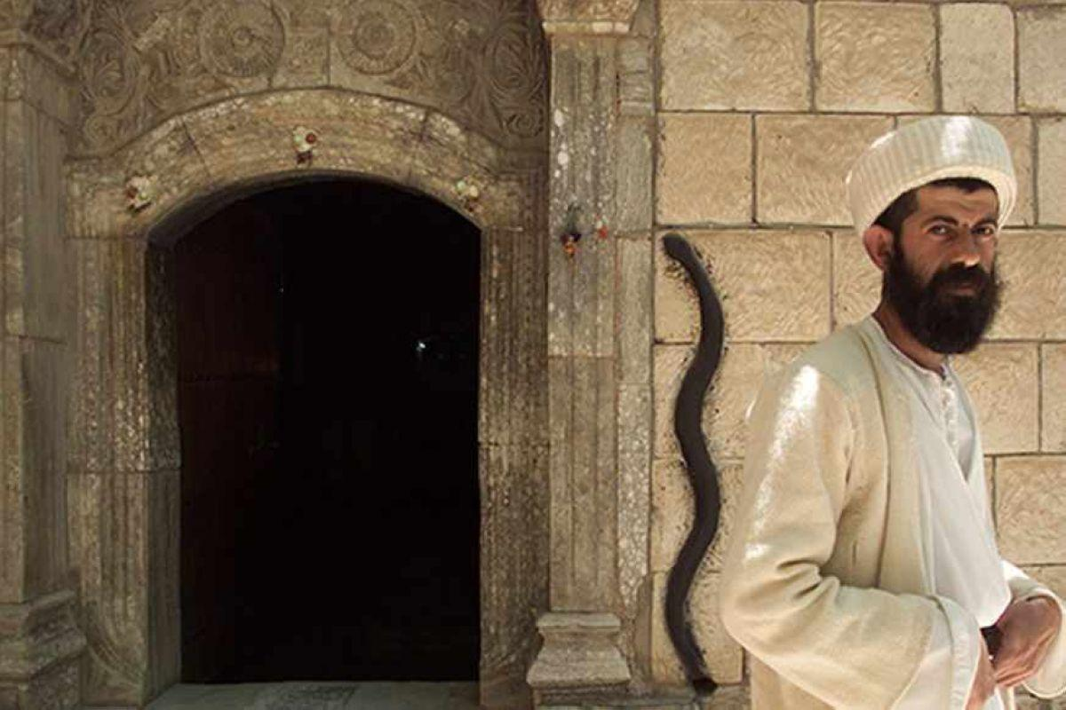 YEZIDI MONK BABA CHAWISH POSES IN FRONT OF ENTRANCE TO THE LALISH TEMPLE.